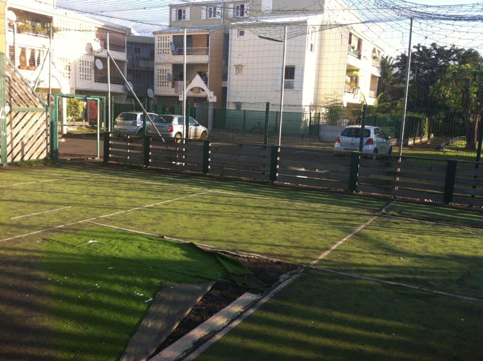 Plateau sportif à l'abandon dans un quartier populaire.